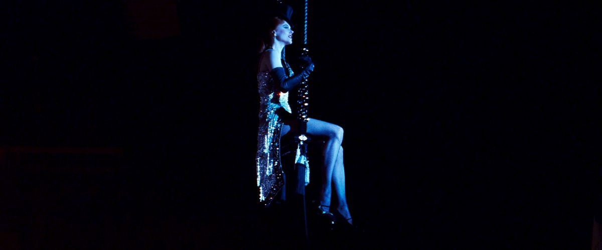 Nicole Kidman, in a spangled leotard, cape, and tophat, sits on a swing in a dark room in Moulin Rouge