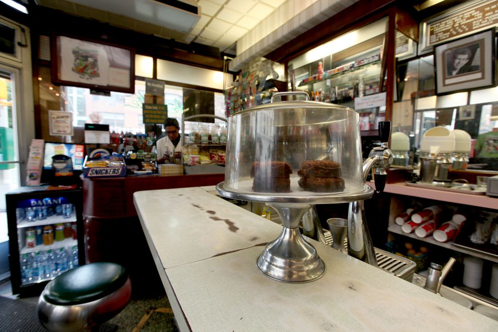 A diner counter with a cake inside a cake stand