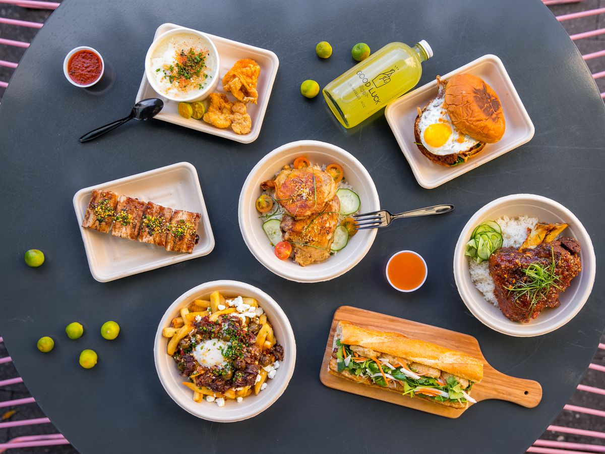 Dark table with colorful Filipino dishes from Spoon & Pork restaurant.