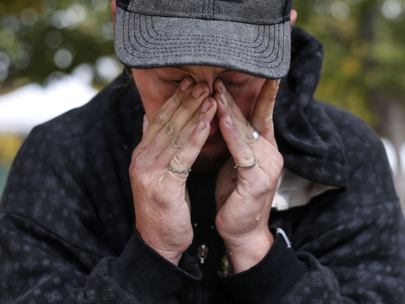 Christopher Hovey wipes his eyes after rinsing his face and hair with a bottle of water at Taufer Park in Salt Lake City on Friday, Oct. 23, 2020.