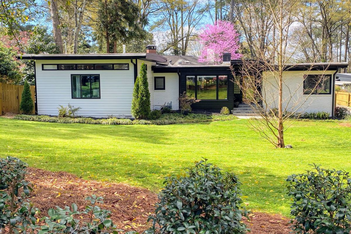 A low white midcentury house with a very green yard and pink tree behind it.