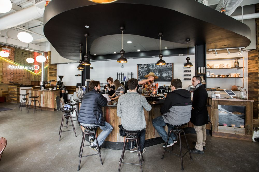 Customers in jackets and sweaters gather around a curved bar sitting at stools.