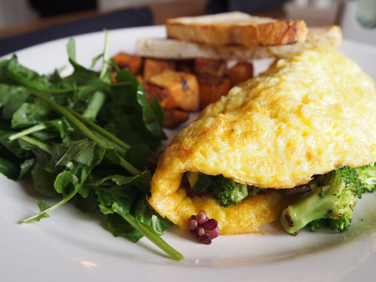 An omelet served with greens and toast.