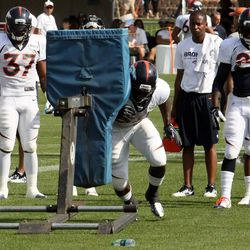Broncos running backs look on as Montee Ball connects with the sled