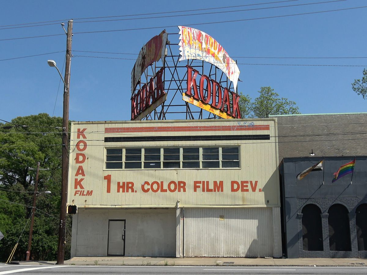 Two-story building with large KODAK sign on the roof.