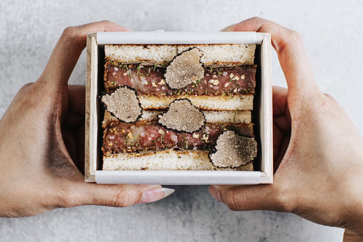 a Japanese sando in a box, held by two hands, topped with gold leaf and truffles