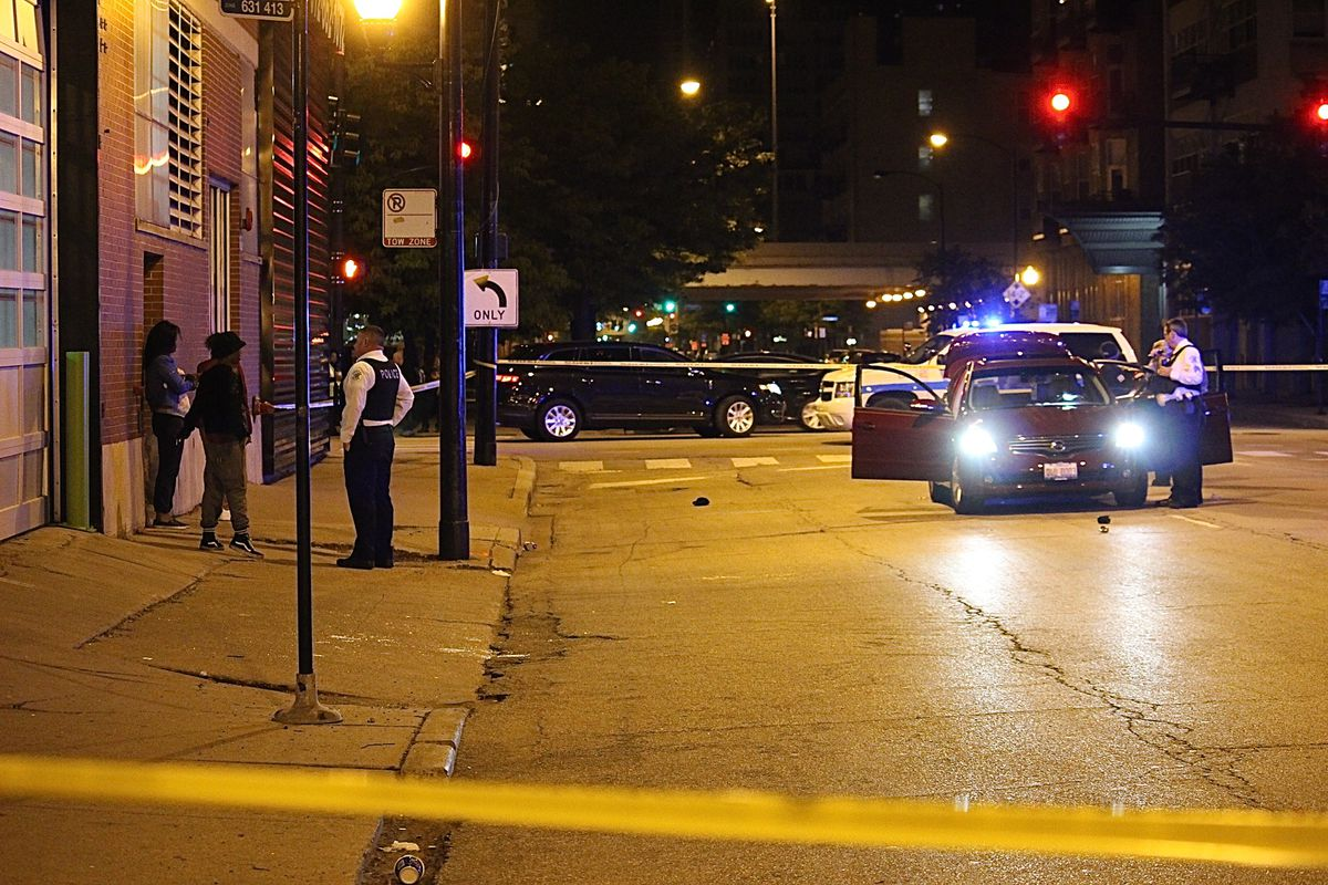 Police officers speak to witnesses at a shooting that left two people wounded early Thursday. | Daniel Brown/Sun-Times
