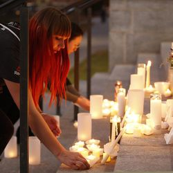 Samantha Stewart leaves a candle on the steps during a candlelight vigil for ChenWei Guo at the University of Utah in Salt Lake City on Wednesday, Nov. 1, 2017. Guo who was shot and killed during a car jacking.