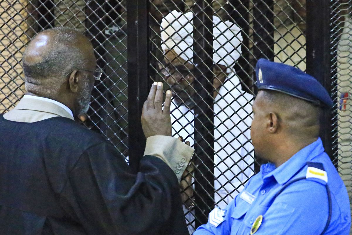 Al-Bashir sits in a cage as a judge speaks to him, and a law enforcement official looks on.