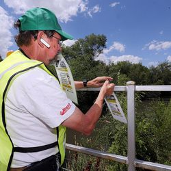 Charlie Eckhardt, of Salt Lake City Community Emergency Response Teams, posts a sign in Salt Lake City on Monday, July 18, 2016, warning of possible toxic algae contamination in the Jordan River.