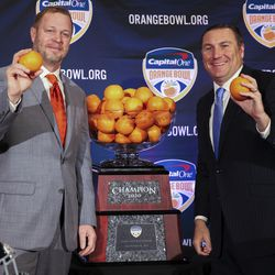 Virginia Cavaliers head coach Bronco Mendenhall, left, and Florida Gators head coach Dan Mullen, right, pose for a photograph during a news conference for the Orange Bowl NCAA college football game, Sunday, Dec. 29, 2019, in Fort Lauderdale, Fla. Florida plays Virginia in the Orange Bowl on Dec. 30.