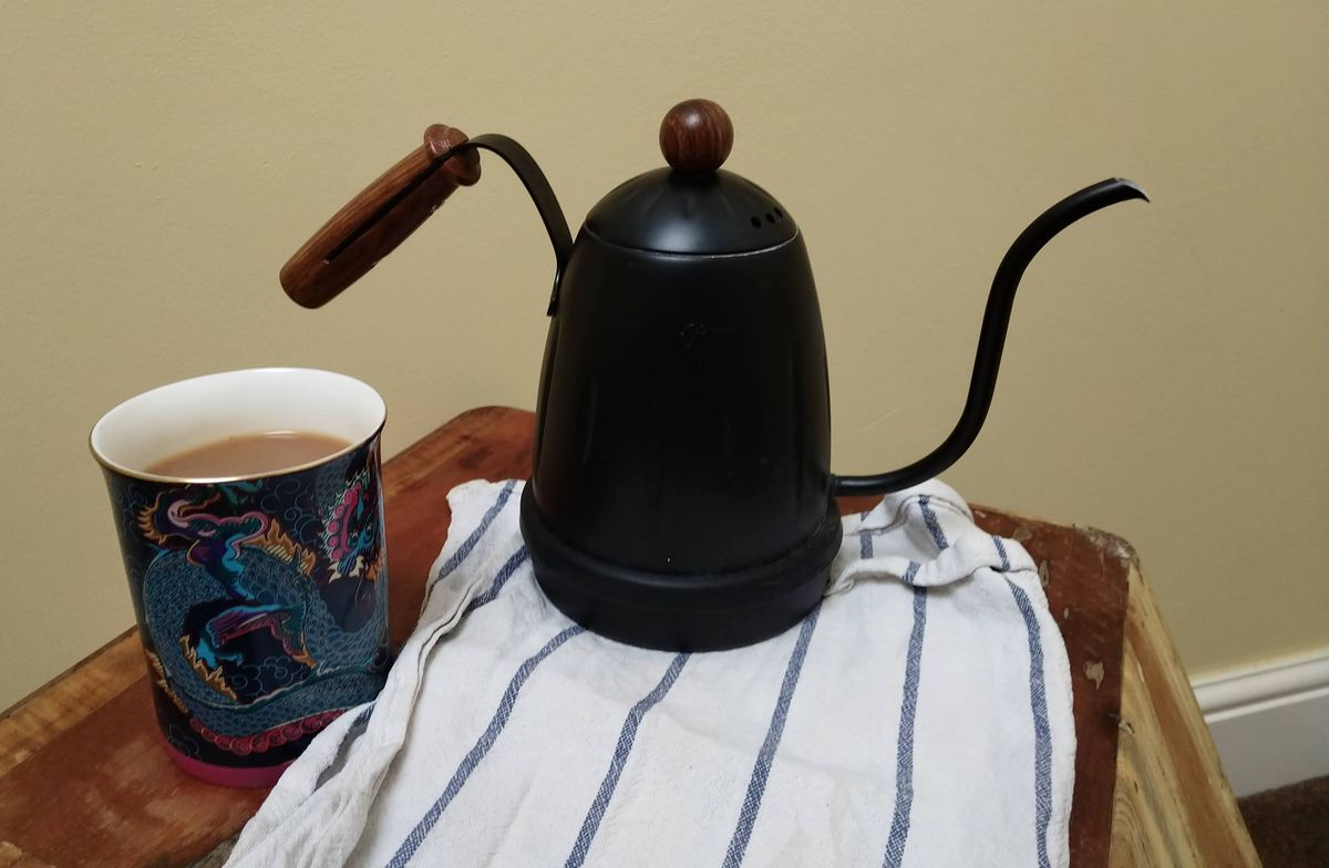 a gooseneck kettle with a cup of tea