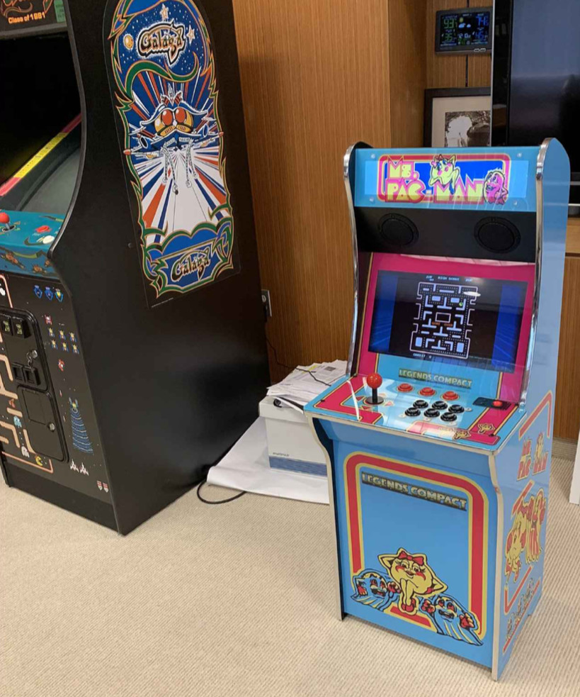 Image showing a miniaturized version of a Ms. Pac-Man arcade cabinet next to a full-size Galaga cabinet