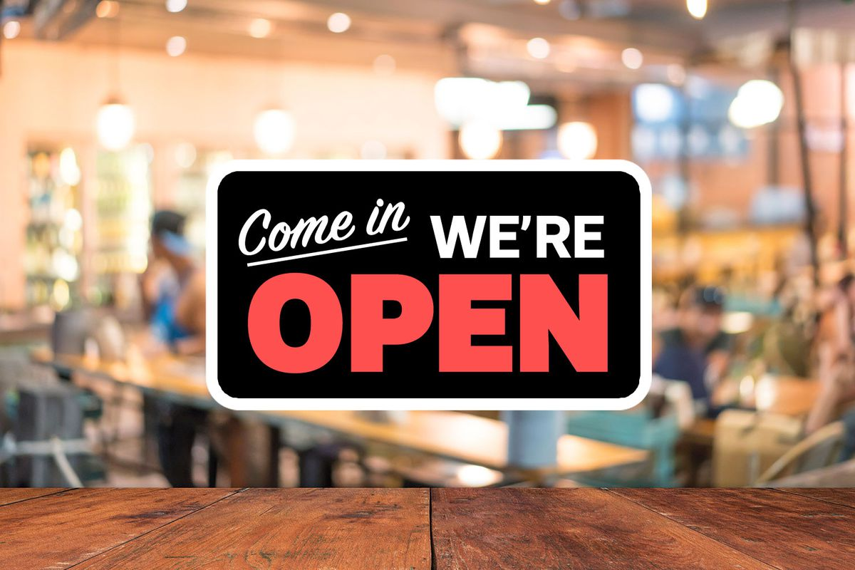 A stock photo of a now open sign with an out of focus dining room visible behind it