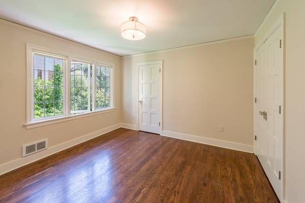 A bedroom with hardwood floors and multi-pane windows