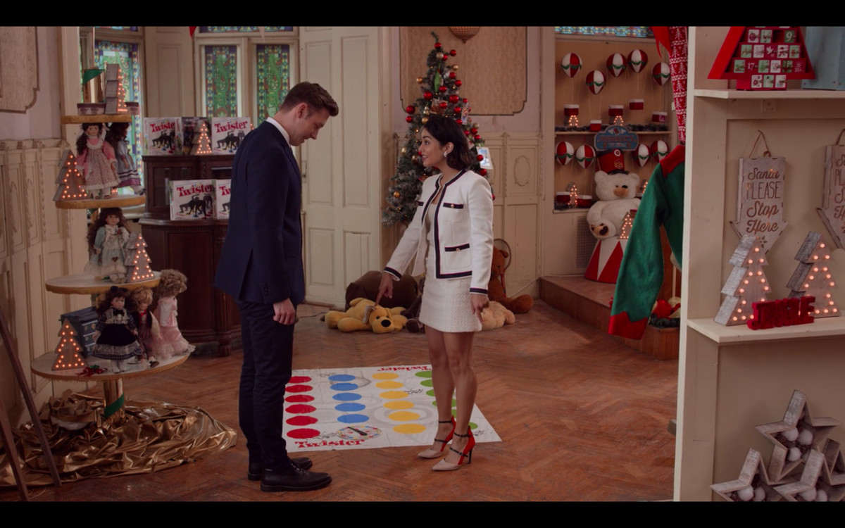 Kevin and Stacy standing in an old-timey toy store and pointing at a Twister mat