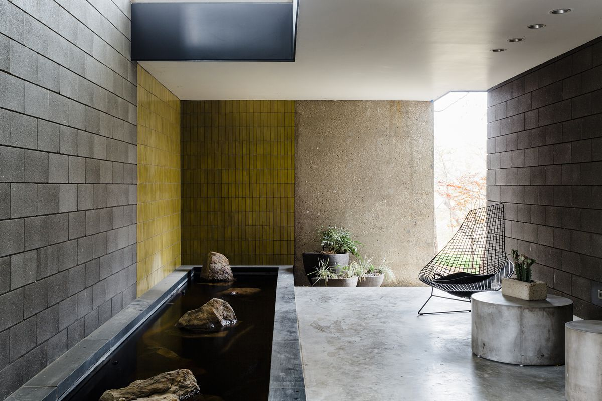A covered patio has a long koi pond decorated with boulders that peek above the water. A yellow tile wall is a bright accent.