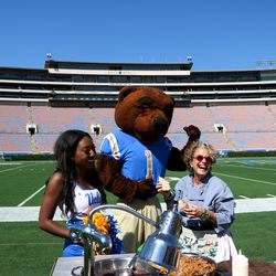 Sue Feniger of Border Grill poses with Joe Bruin and a member of the UCLA Spirit Squad.