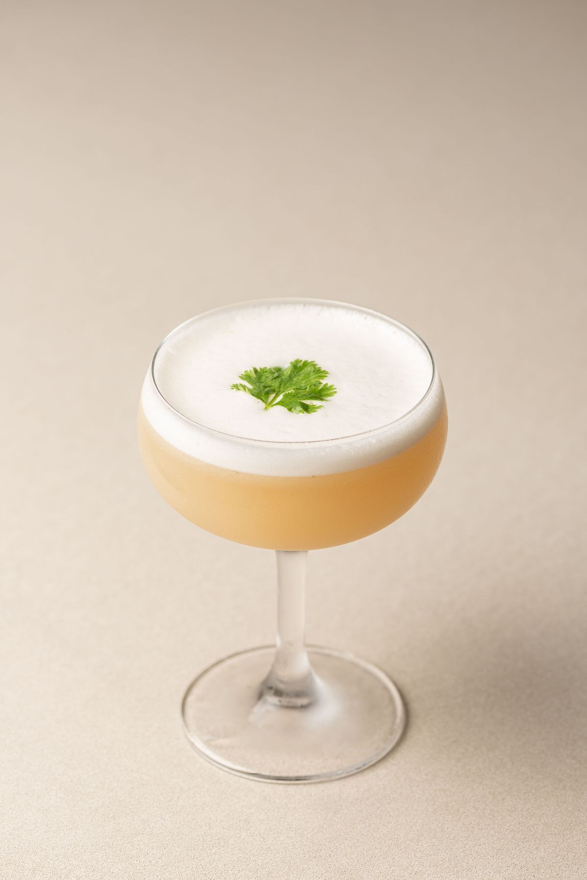 A frothy cocktail in light orange with a coupe glass on a white table.