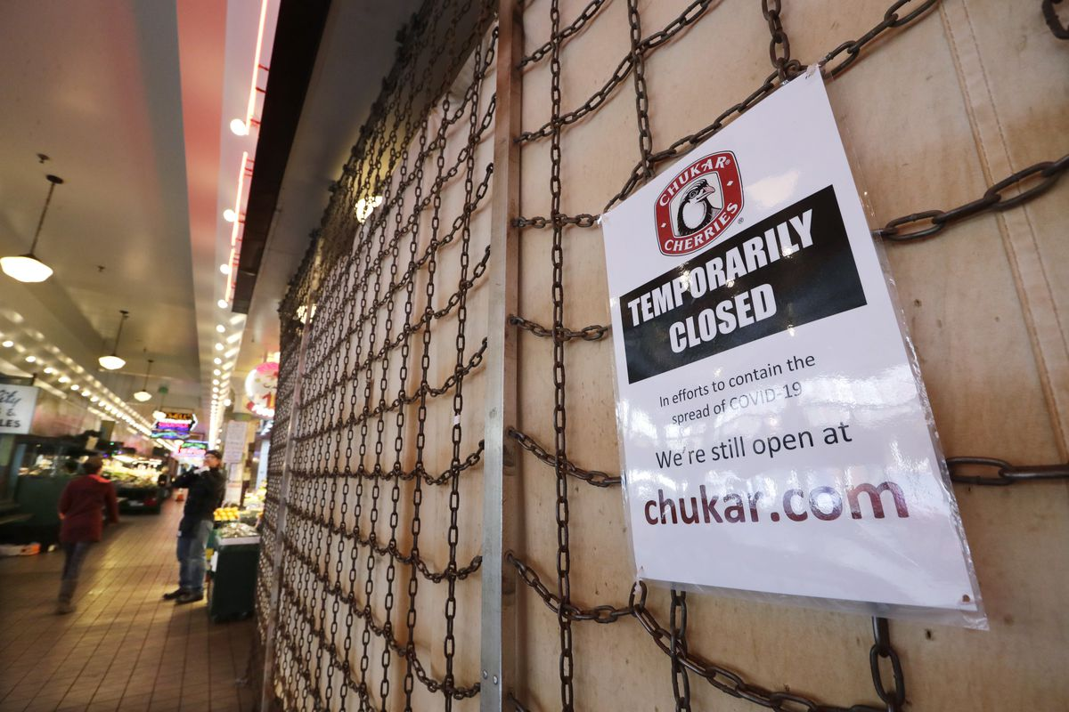 a sign explains the closure of a shop in the Pike Place Market in Seattle