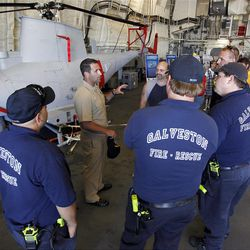 Master Chief Mike Lombardo gives Galveston firefighters a tour of a mission bay aboard the Fort Worth on Thursday Sept. 20, 2012 at Pier 21 in Galveston, Texas. The newest vessel in the Navy's Littoral Combat Ship program will be commissioned Saturday in Galveston. (AP Photo/The Daily News, Jennifer Reynolds)