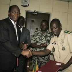 Coup leader Capt. Amadou Haya Sanogo, right, shakes hands with Burkina Faso Foreign Minister Djibrill Bassole, after signing an accord agreeing to return the country to constitutional rule, in Sanogo's office at junta headquarters in Kati, outside Bamako, Mali Friday, April 6, 2012. Under intense pressure from the nations bordering Mali, Sanogo, the junior officer who seized control of the country in a coup last month signed an accord agreeing to return the country to constitutional rule. The announcement was made late Friday, only hours after separatist rebels in the country's distant north declared their independence.