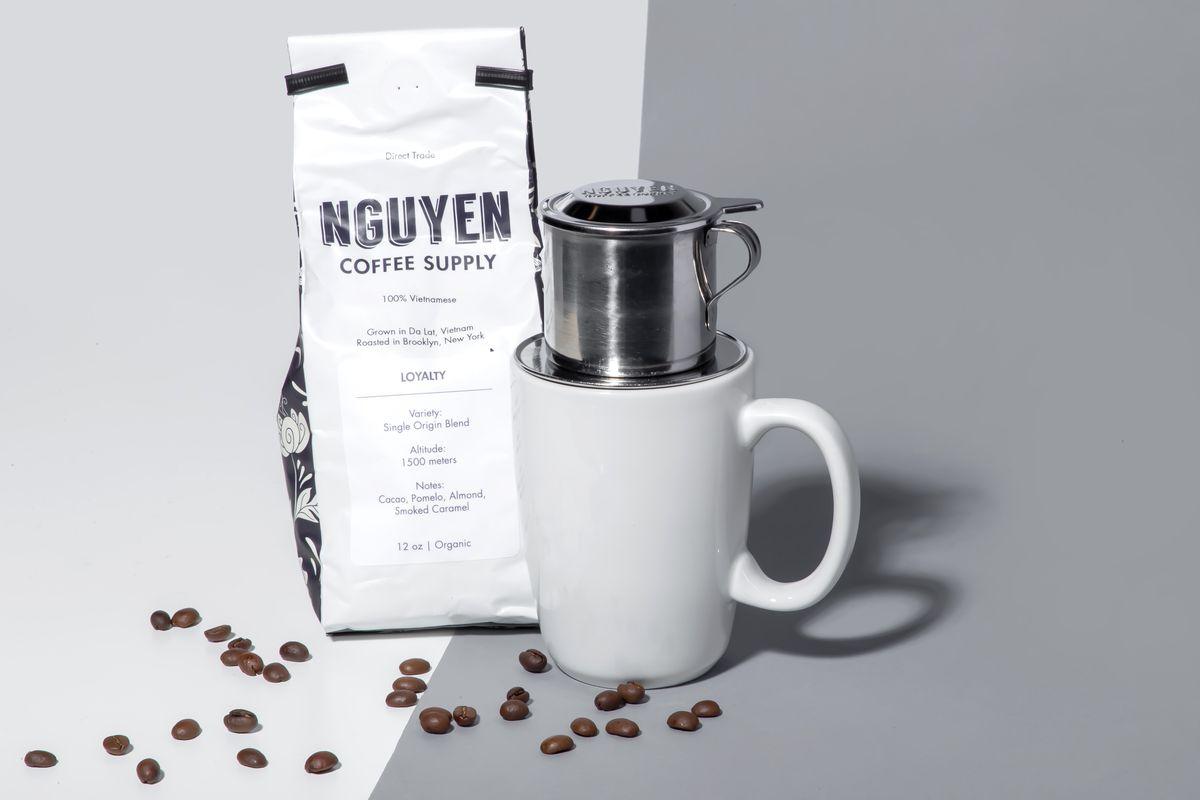 A bag of coffee next to a mug