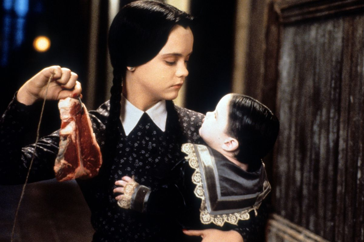 Christina Ricci as Wednesday Addams in 'Addams Family Values' holds a baby dressed in ruffles in one arm and a steak in the other, in a long Victorian hallway with dark wood panelling.