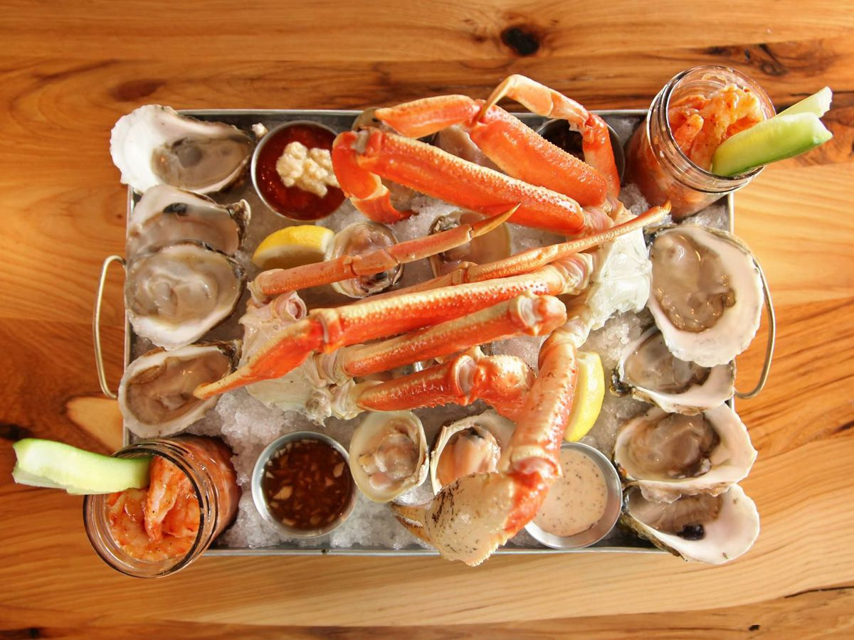 Overhead view of a rectangular silver platter full of ice and raw seafood, including oysters, crab legs, and more. The platter is on a wooden table.