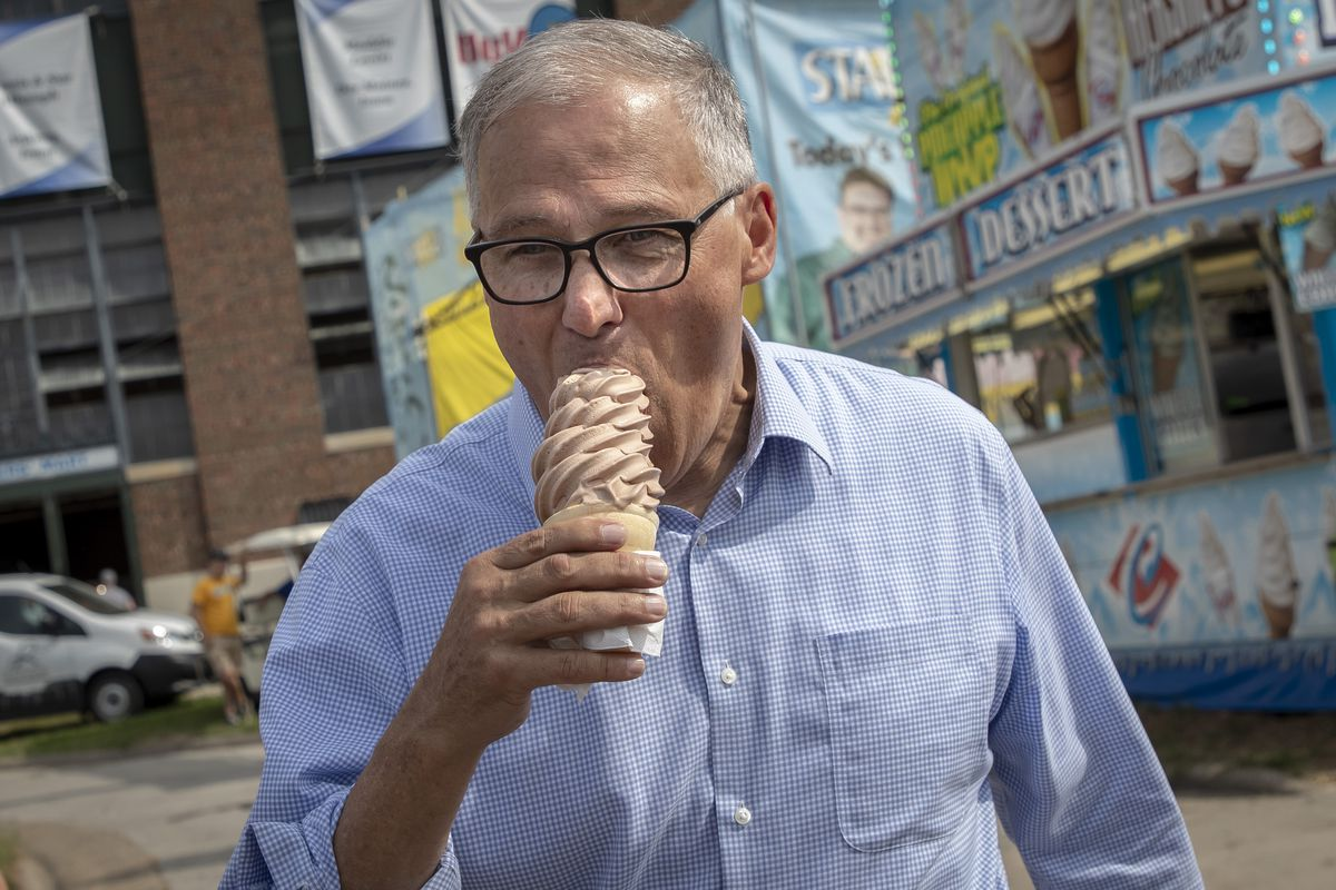Jay Inslee walking away from an ice cream stand, biting into a cone of soft serve.