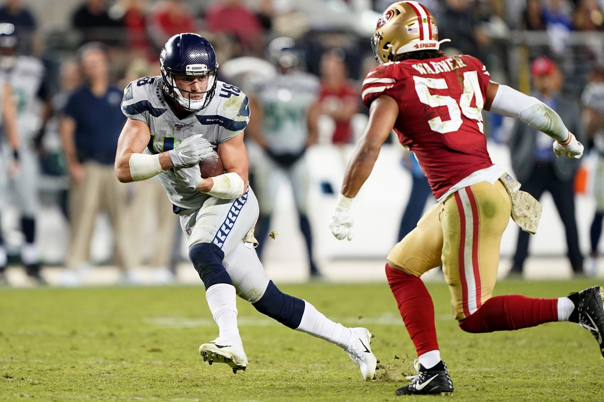 Jacob Hollister of the Seattle Seahawks runs with the ball pursued by Fred Warner of the San Francisco 49ers during overtime of an NFL football game at Levi's Stadium on November 11, 2019 in Santa Clara, California.