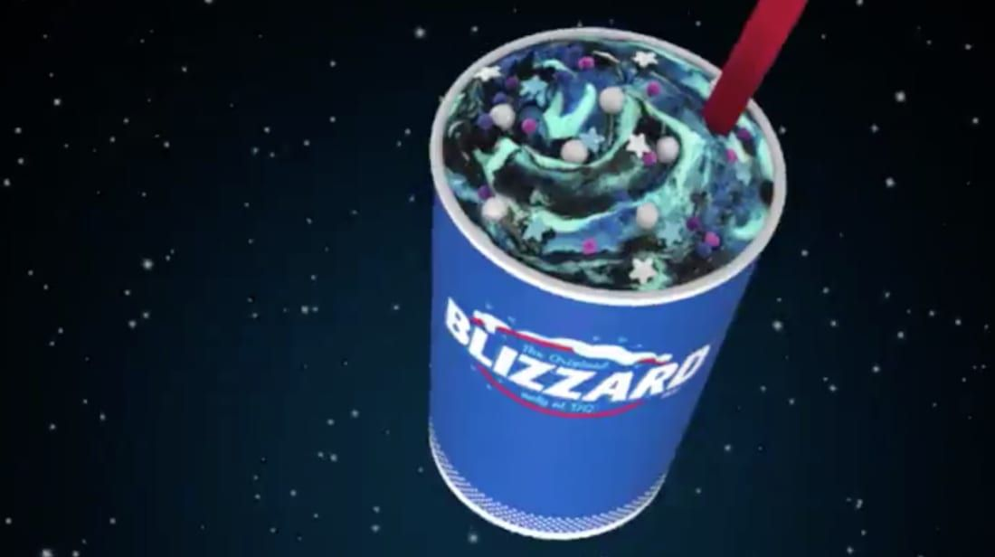 Blue cup with a green, purple, and blue drink with a red straw.