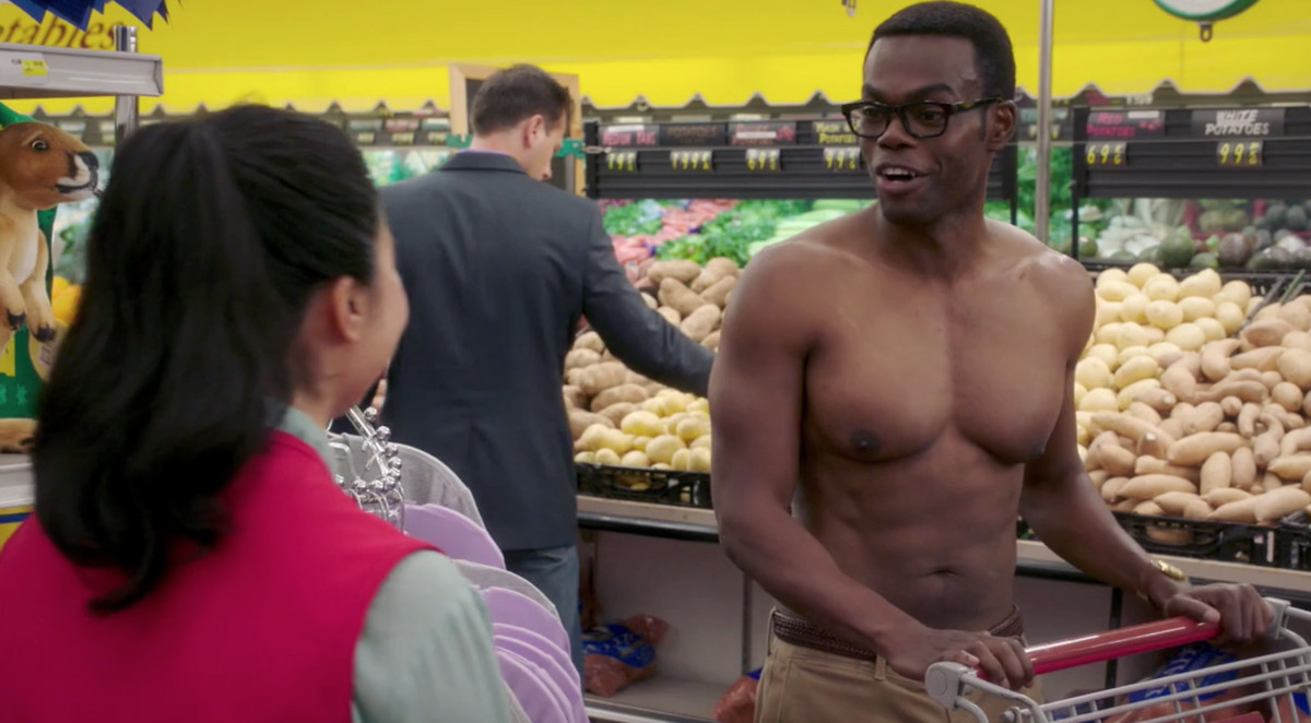Chidi standing shirtless in the grocery store