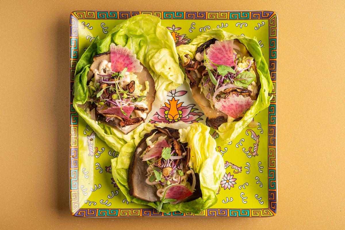 Mushroom lettuce tacos on a green patterned plate.