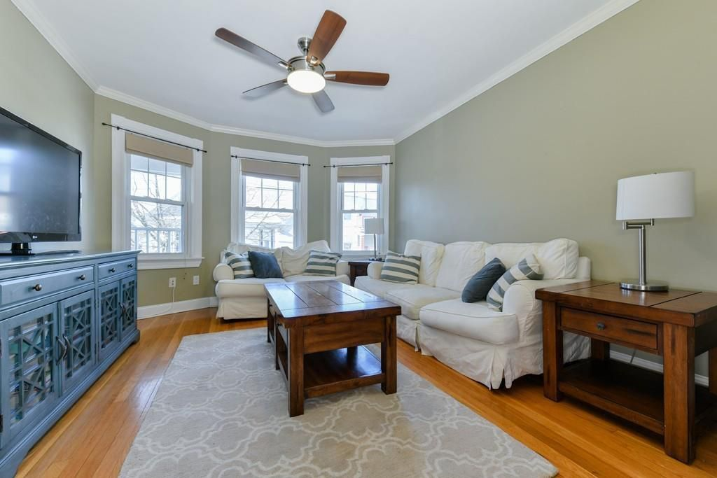 A slender living room with a couch facing a TV, and there's a ceiling fan above and a bay window at the end.