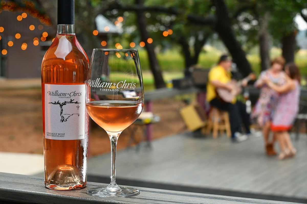 """In the foreground, a bottle of rosé wine with a label reading """"William Chris Vineyards"""" next to a glass of wine; in the background, a couple dancing and a person playing a guitar outside."""