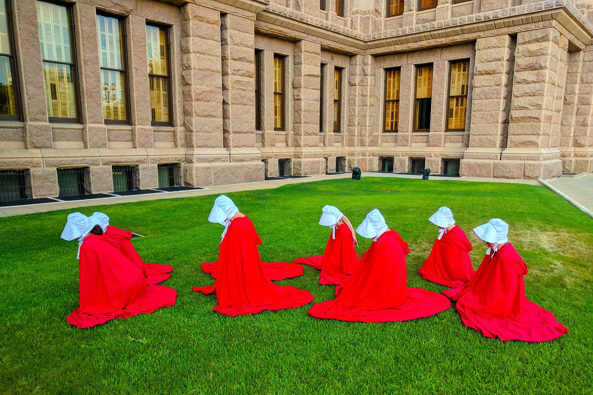 People in long red robes and white bonnets bowing on lawn of Capitol building