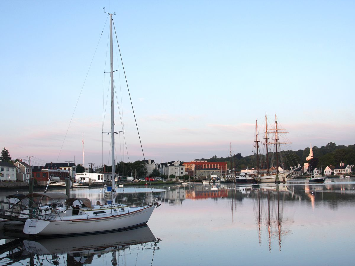 A boat marina with various assorted boats sitting in a body of water. There is a sunset with pink clouds.