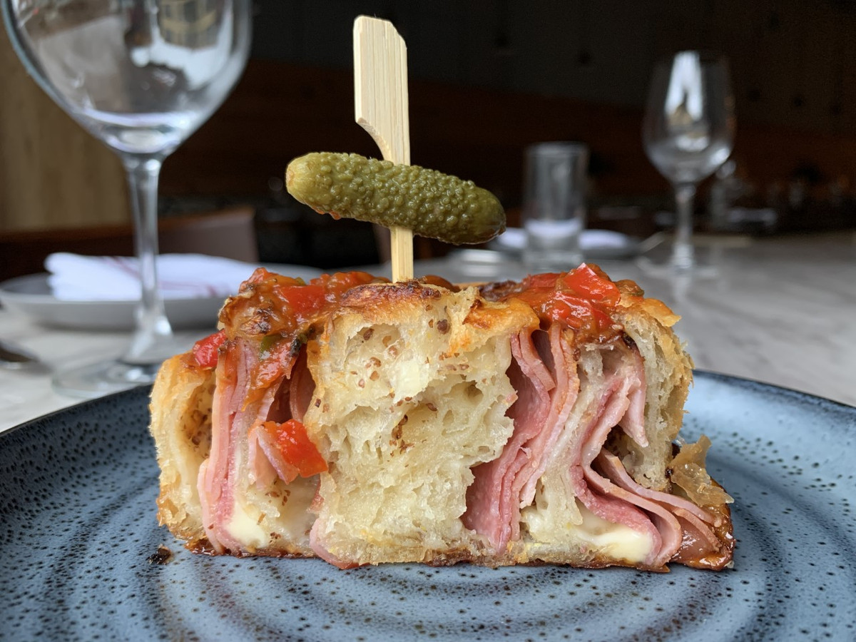 Cross-section of a croissant with slices of deli meat among its layers and a tomato relish on top. A small pickle on a toothpick is also coming out of the top. It sits on a pretty blue plate in a restaurant.