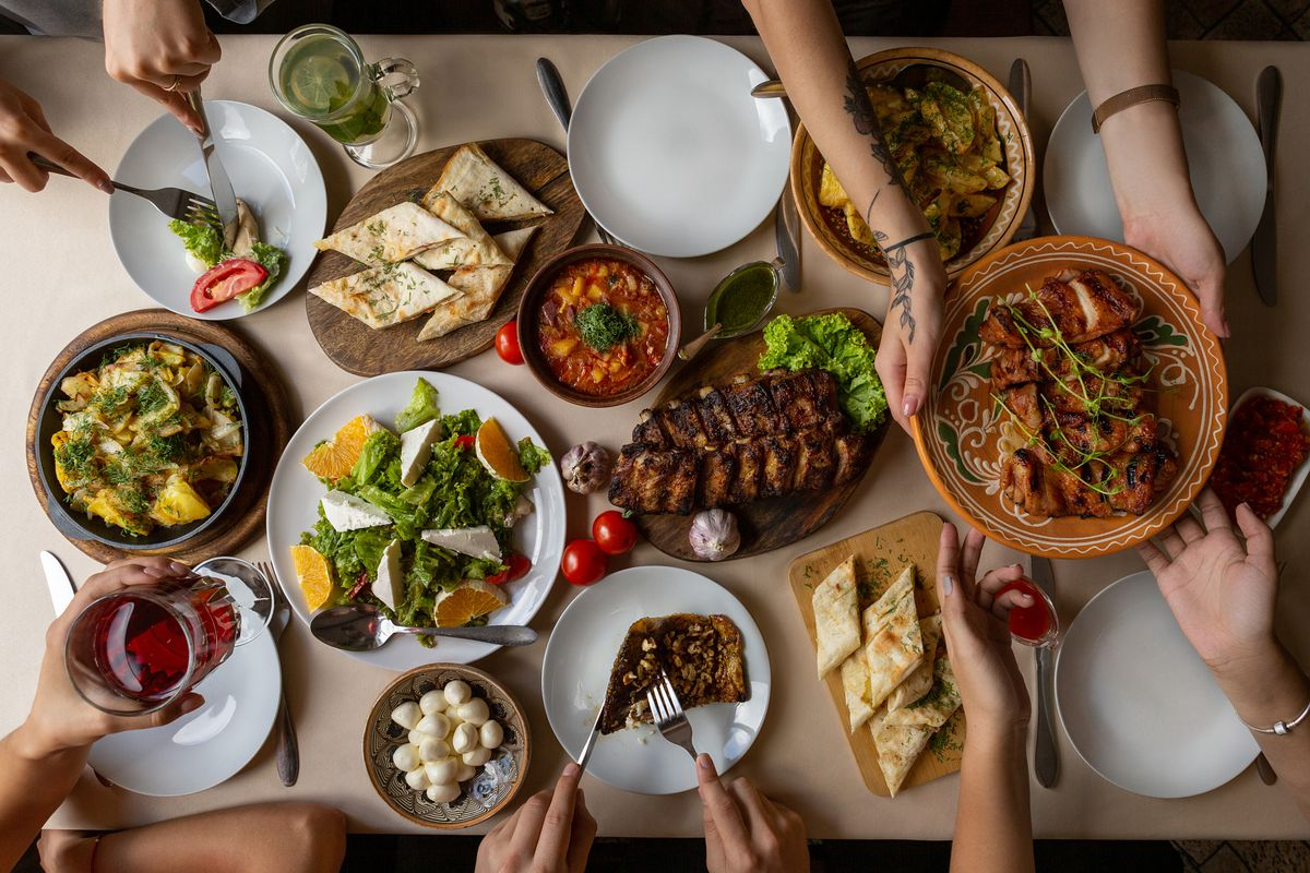 An overhead shot of a table filled with food and hands reaching across to share it