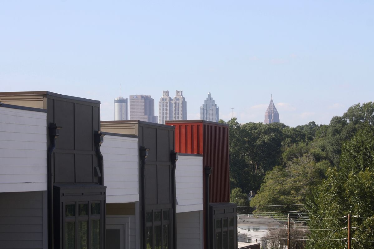 A new building shown against trees and a skyline in the distance.