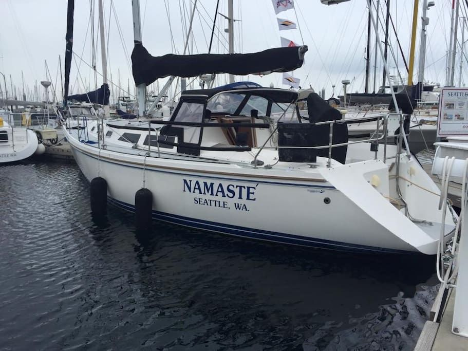 """A white sailboat with metal railings and a lowered, navy blue sail on the water. In navy blue, the side reads, """"NAMASTE, SEATTLE, WA."""""""