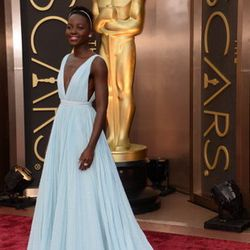 Lupita Nnyong'o wore a baby blue Prada gown with pleating and a deep V-neck, which you can find at the Prada boutique at the Shops at Crystals. She was inspired by champagne bubbles plus the blue reminded her of home.