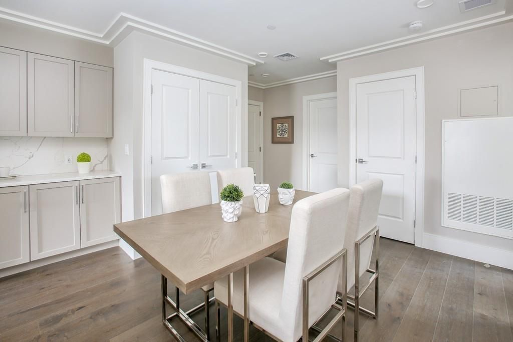 A new-looking dining room with a table and chairs.