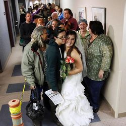 Jax Collins, left, hugs Heather Collins as they wait to get a marriage license outside the Salt Lake County clerk's office, Monday, Dec. 23, 2013. U.S. District Judge Robert Shelby denied a motion by the state of Utah to halt same-sex marriages pending an appeal.