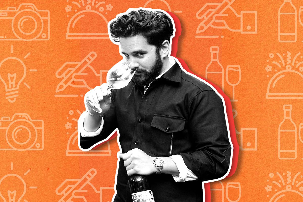 A cut out black and white image of Charles Bililies with curly dark hair and a beard sniffing a glass of wine on a bright orange illustrated background.