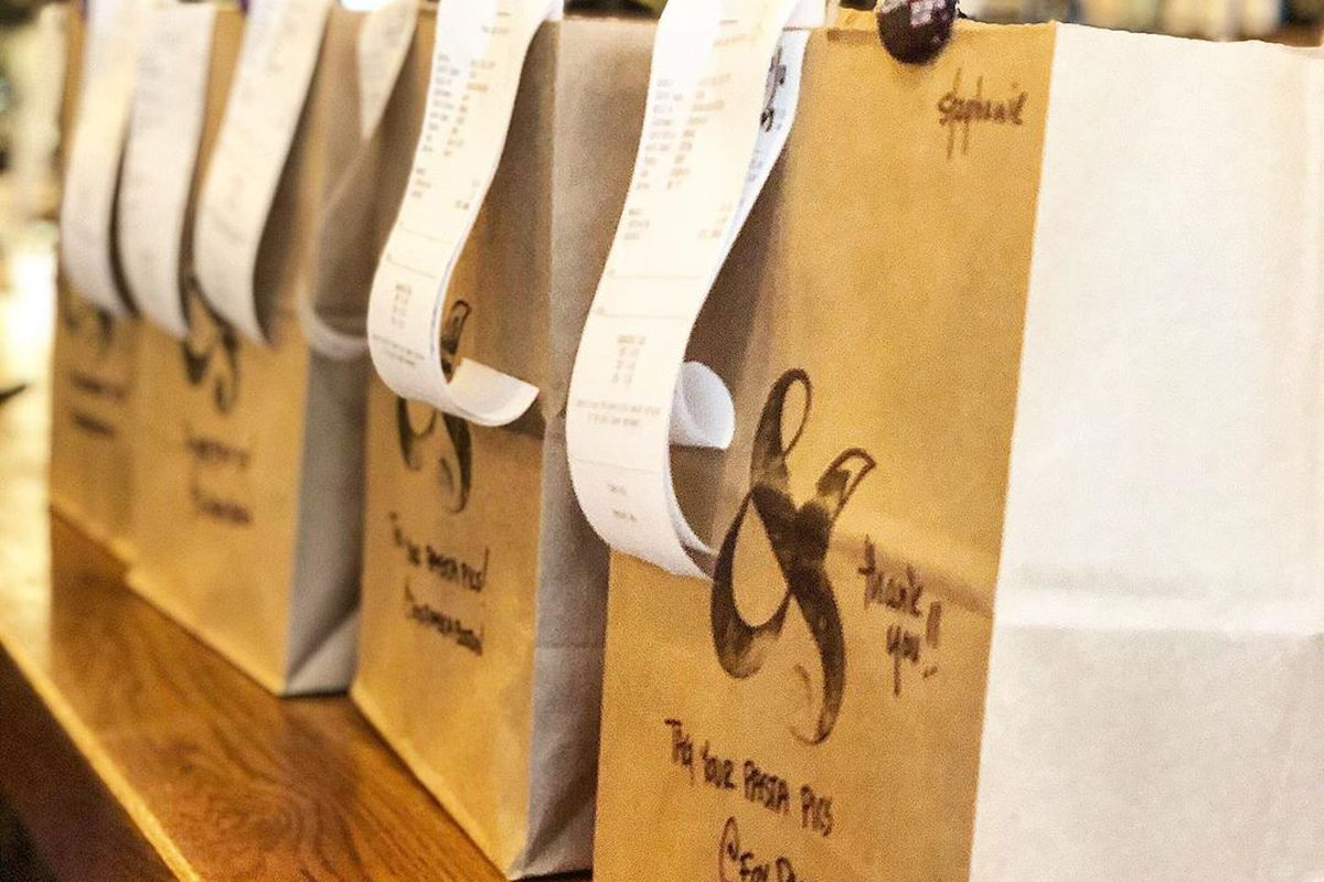 Brown paper delivery bags with receipts stapled to them, lined up on a restaurant kitchen counter