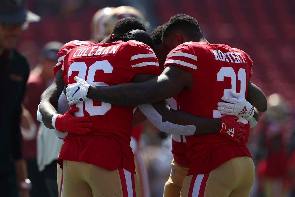 San Francisco 49ers running backs Tevin Coleman, Raheem Mostert, and Matt Breida embrace during warmup against the Los Angeles Rams at Los Angeles Memorial Coliseum on October 13, 2019 in Los Angeles, California.
