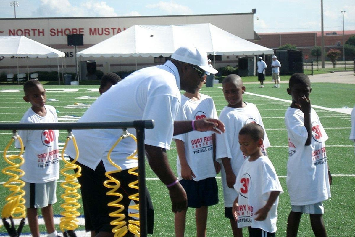 The Baltimore Ravens' Cory Redding gives a camper some instruction at his 5th Annual 3D (Desire, Discipline, Dedication) Football Camp to benefit Hearts Outreach, Inc.