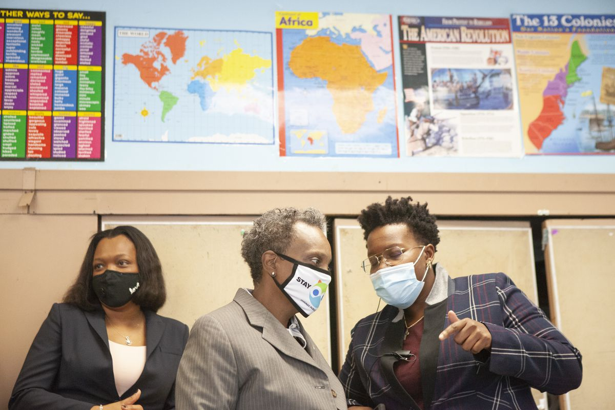 All wearing masks, Mayor Lori Lightfoot talks with Principal Jasmine Thurmond and standing next to school chief Janice Jackson, with maps on the wall behind them.
